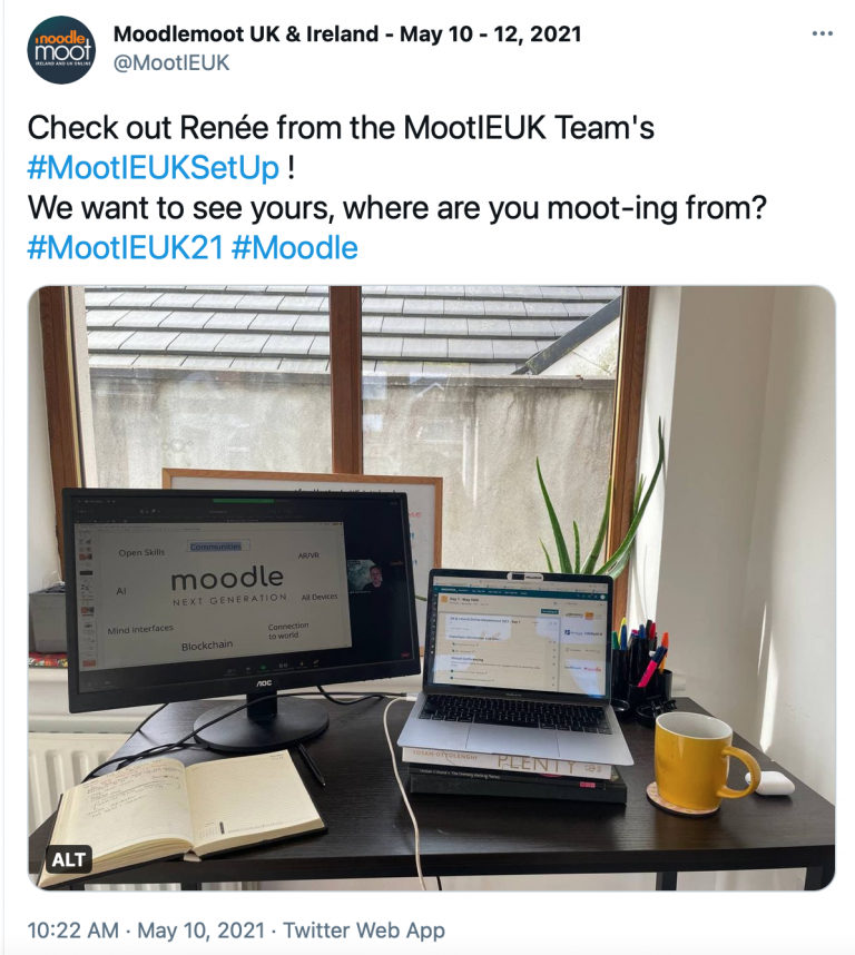 """Screenshot of tweet from user @MootIEUK that reads: """"Check out Renée from the MootIEUK Team's #MootIEUKSetUp ! We want to see yours, where are you moot-ing from? #MootIEUK21 #Moodle"""" with an attached photo of a point of view work desk setup showing a laptop, monitor screen, notebook and mug on desk surface."""