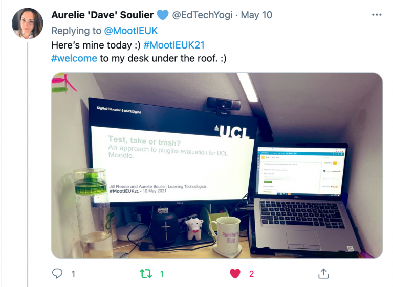 """Tweet from from Aurelie 'Dave' Soulier @EdTechYogi in reply to the previous tweet above that reads: """"Here's mine today :) #MootIEUK21 #welcome to my desk under the roof. :)"""" attached is a photo of a point of view work desk setup showing a laptop, monitor screen, keyboard, lamp, notebook and mug on desk surface."""