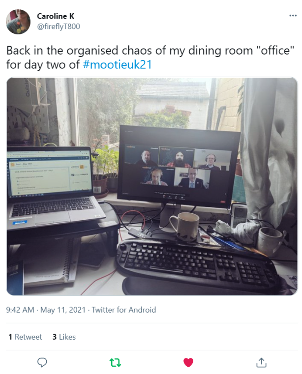 """Tweet from Caroline K @fireflyT800 that reads """"Back in the chaos of my dining room """"office"""" for day two of #mootieuk21 """" with a photo of the users desk point of view featuring a laptop, keyboard, screen monitor, mugs and a notebook."""