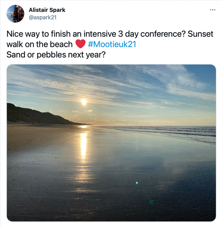 """Tweet from @aspark21 reading """"Nice way to finish an intensive 3 day conference? Sunset walk on the beach #MootIEUK21 Sand or pebbles next year? With photograph of sunset on the beach."""